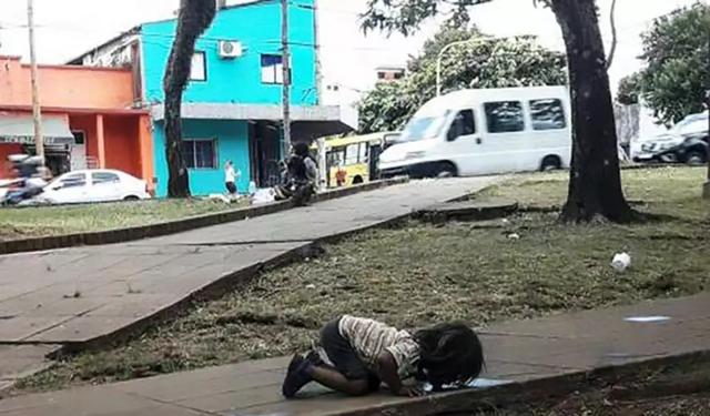 口渴的小女孩跪在地上喝脏水