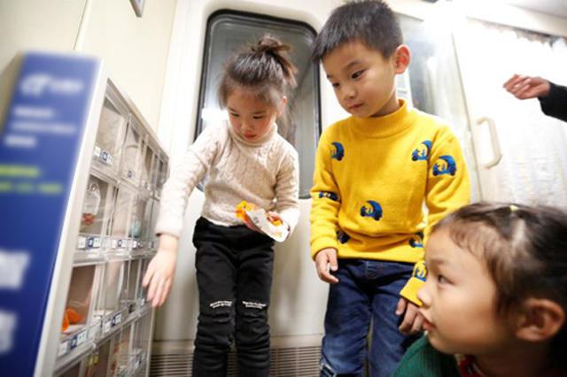 小朋友在体验列车上的自动售货机